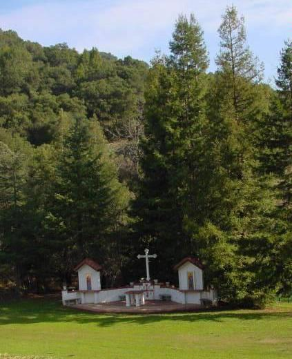Facing East toward the Cross Shrine of Holy Cross Monastery with redwood trees planted by the Fathers in the background